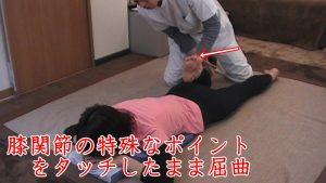 膝関節の皮膚を誘導しつつ屈曲足を抱え上げて少し反らします。この状態で坐骨を押し上げて骨盤を整えます。