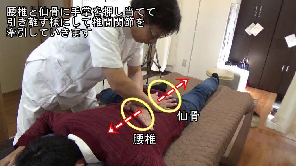 腰椎と仙骨に手掌を押し当てて引き離す様にして椎間関節を牽引していきます