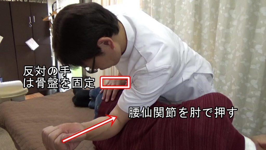 腰仙関節を肘で押して反対の手で骨盤を固定する