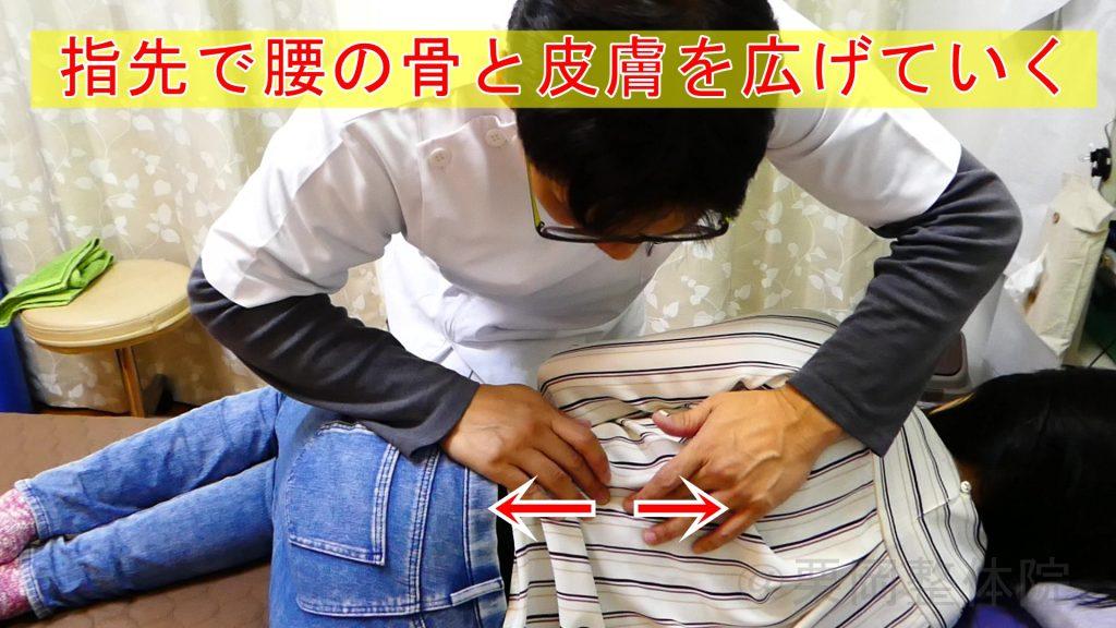 触圧覚刺激法:指先で腰の骨と皮膚を広げていく