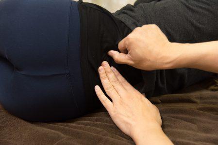 腰を指圧で押さえているポーズ