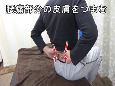 腰痛部分の皮膚をつまむ